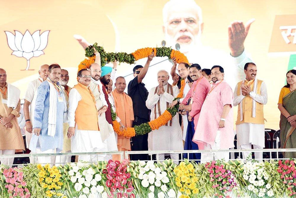 PM नरेन्द्र मोदी का शाहजहांपुर के रोजा में आयोजित 'किसान कल्याण रैली' में स्वागत करते हुए