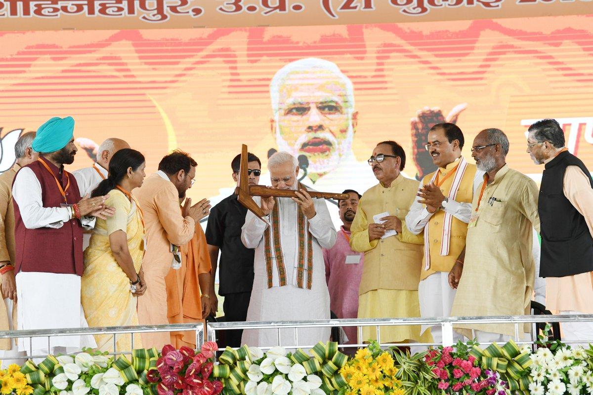 PM नरेन्द्र मोदी को शाहजहांपुर के रोजा में आयोजित 'किसान कल्याण रैली' में हल भेंट करते हुए