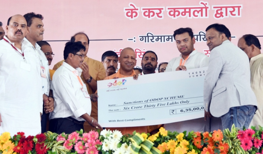 UPCM अलीगढ़ में लाभार्थियों को चेक प्रदान करते हुए