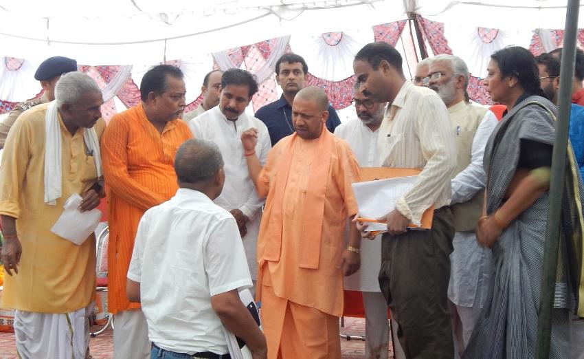 UPCM योगी बलिया में बाढ़ पीड़ितों को राहत सामग्री का वितरण करते हुए
