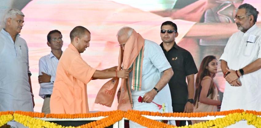 मुख्यमंत्री योगी आदित्यनाथ मथुरा में पुष्प एवं गमछा भेंट कर प्रधानमंत्री का स्वागत करते हुए