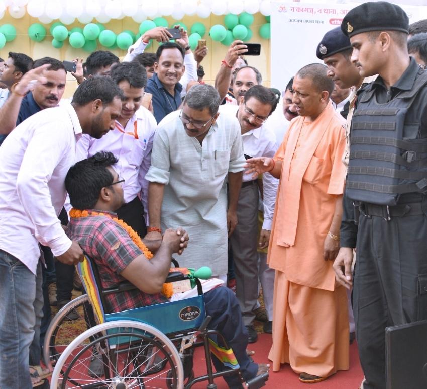 UPCM प्रतापगढ़ में लाभार्थी को ट्राई साइकिल प्रदान करते हुए